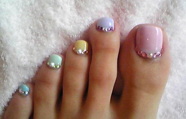 Diseño de uñas de los pies con esmalte y piedras